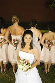 Hispanic bride in front of bridesmaids — Stock Photo