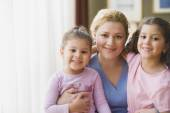 Hispanic mother hugging daughters indoors — Stock Photo