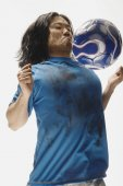 Asian male soccer player bouncing ball on chest — Stock Photo