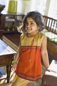 Indian girl standing in livingroom — Stock Photo