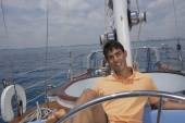 Hispanic man steering sailboat with foot — Foto Stock
