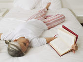 Asian woman reading on bed — Stockfoto