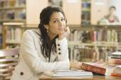 Mixed Race woman with books in library — Stock Photo