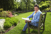 Hispanic man reading in backyard — Stockfoto
