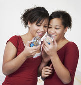 African twin sisters looking at snow globes — Stock Photo