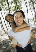 Mixed Race father giving daughter piggyback ride — Stock Photo