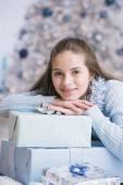 Teenaged girl leaning on Christmas gifts — Stock Photo