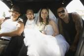 Hispanic newlyweds and family in limousine — 图库照片