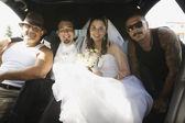 Hispanic newlyweds and family in limousine — Stockfoto