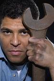 Hispanic man holding large wrench — Stockfoto