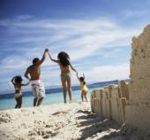 Hispanic family with sand castle in foreground — Foto de Stock