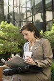 Hispanic businesswoman reading newspaper — Stock Photo