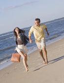 Hispanic couple running on beach — Stock Photo