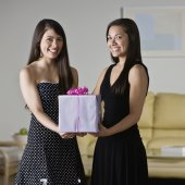 Asian sisters holding gift — Stock Photo