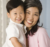 Asian mother hugging son — Stock Photo