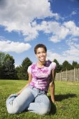African American woman sitting in grass — Stockfoto