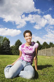 African American woman sitting in grass — Stock Photo