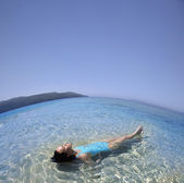 Pacific Islander woman laying in ocean — Stock Photo