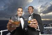 Multi-ethnic men in tuxedos toasting — Stock Photo