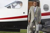Mixed Race businessman exiting airplane — Stock Photo
