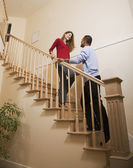 Multi-ethnic couple standing on stairs — Stock Photo