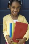 African girl holding school books — Stock Photo