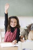 Girl raising hand in class — Stock Photo
