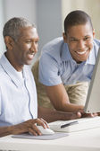 African American father and adult son looking at computer — Stock Photo