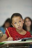 Menina asiática na mesa na sala de aula — Fotografia Stock