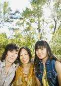 Asian mother and adult children hugging — Stock Photo