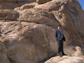 African businessman standing on rock — Stock Photo
