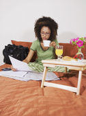 African woman eating breakfast in bed — Stock Photo