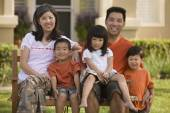 Asian family sitting on bench — Stock Photo