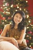 Asian woman in front of Christmas tree — Stock Photo