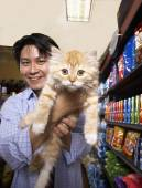 Asian man holding cat in pet store — Stock Photo