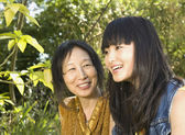 Asian mother and adult daughter outdoors — Stock Photo