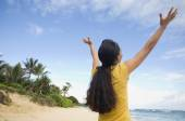 Pacific Islander woman with arms raised at beach — Stock Photo