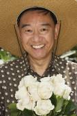 Senior Asian man holding flowers — Stock Photo