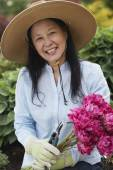 Senior Asian woman holding flowers — Stockfoto