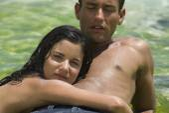 Hispanic couple laying on rock in water — Stock Photo