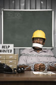 Male worker chained up behind desk — Stock Photo