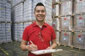 Hispanic man with clipboard smiling in warehouse — Stock Photo