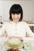 Asian woman sitting at set table — Stock Photo