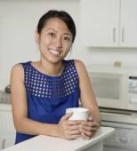 Asian woman holding coffee mug — Stock Photo