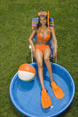 Hispanic woman in bikini next to kiddie pool — Stock Photo