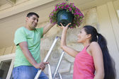 Multi-ethnic couple hanging plant — Stock Photo