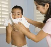 Asian mother helping son put on shirt — Stockfoto