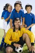 Multi-ethnic children with soccer coach — Stock Photo