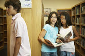Multi-ethnic girls looking at boy in library — Stock Photo