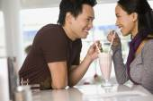 Asian couple sharing milkshake — Stock Photo
